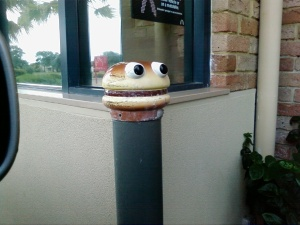 Macca's burger monster sculpture on drive-thru bollard